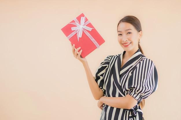 Portret mooie jonge aziatische vrouw met rode geschenkdoos