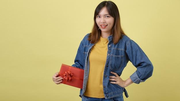 Portret mooie jonge aziatische vrouw met rode giftdoos op geïsoleerd geel