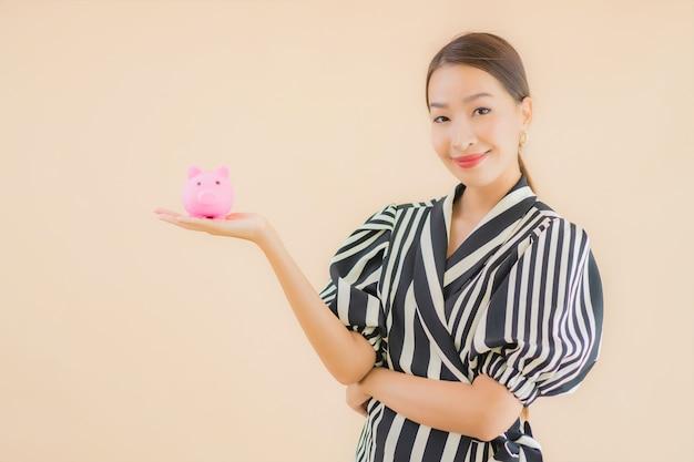 Portret mooie jonge aziatische vrouw met roze spaarvarken