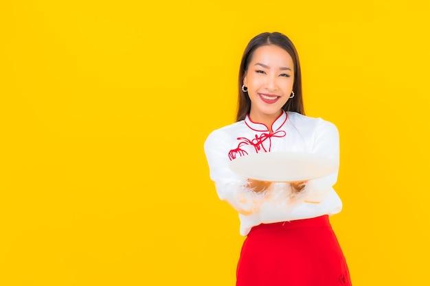 Portret mooie jonge aziatische vrouw met schotelplaat op geel on