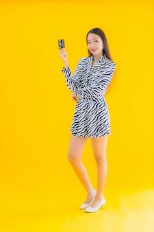 Portret mooie jonge aziatische vrouw met slimme mobiele telefoon en creditcard op geel