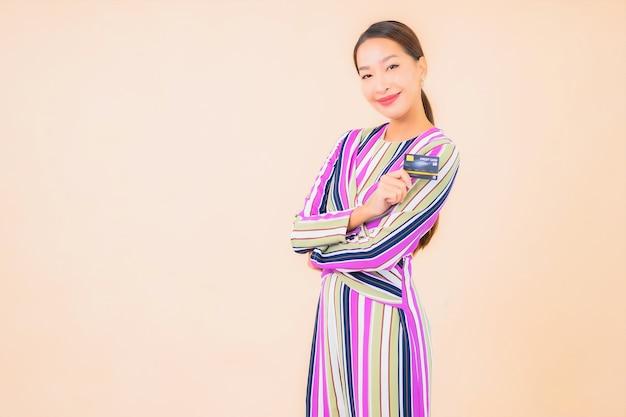 Portret mooie jonge aziatische vrouw met slimme mobiele telefoon en creditcard op kleur