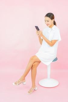 Portret mooie jonge aziatische vrouw met slimme mobiele telefoon op roze kleurenmuur