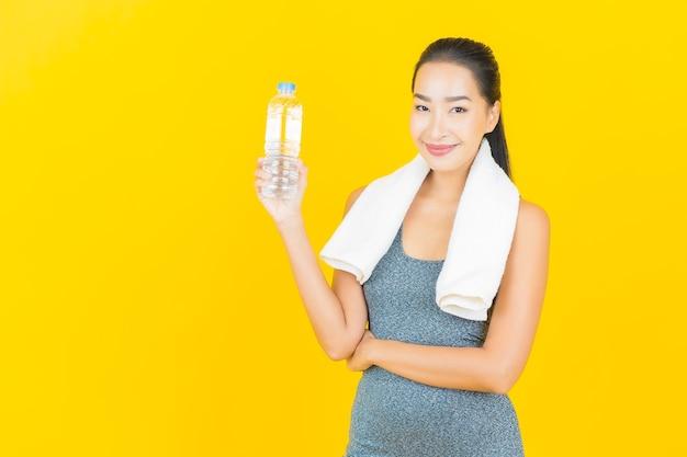Portret mooie jonge aziatische vrouw met sportkleding en flessenwater op gele muur