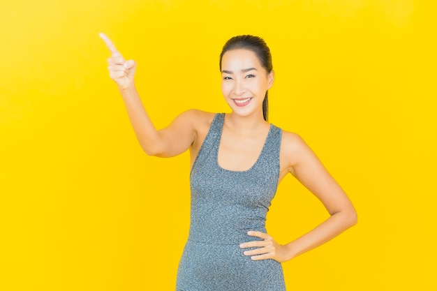 Portret mooie jonge aziatische vrouw met sportkleding klaar voor oefening op gele muur