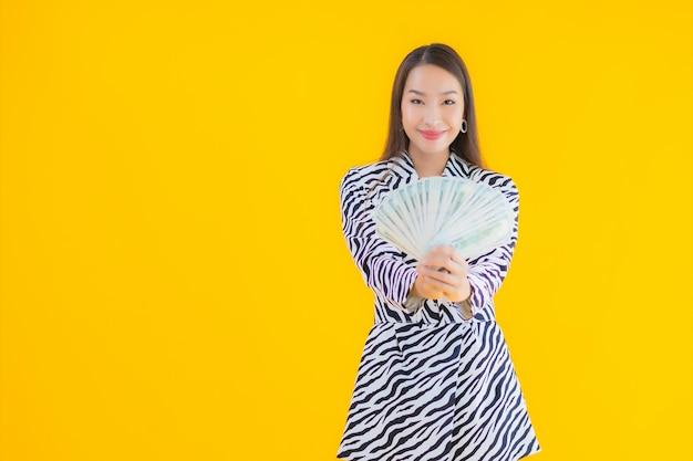 Portret mooie jonge aziatische vrouw met veel contant geld en geld op geel
