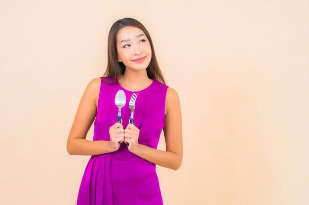 Portret mooie jonge aziatische vrouw met vork en lepel klaar om op kleurenachtergrond te eten