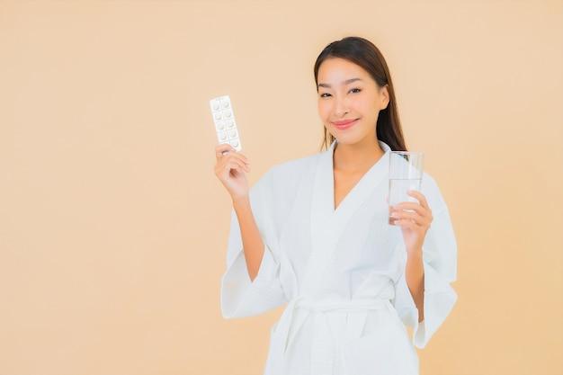 Portret mooie jonge aziatische vrouw met waterglas en drugpil op beige