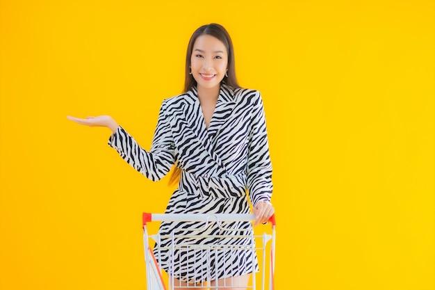 Portret mooie jonge aziatische vrouw met winkelwagentje voor boodschappen op geel