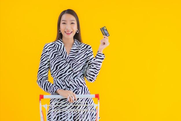 Portret mooie jonge aziatische vrouw met winkelwagentje voor boodschappen op geel Gratis Foto