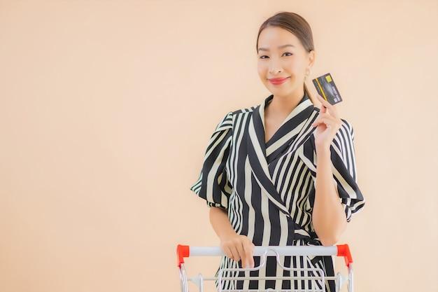 Portret mooie jonge aziatische vrouw met winkelwagentje