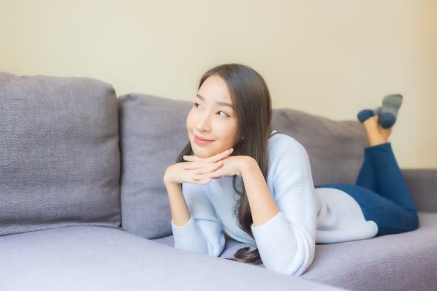 Portret mooie jonge aziatische vrouw ontspannen glimlach op de bank in de woonkamer
