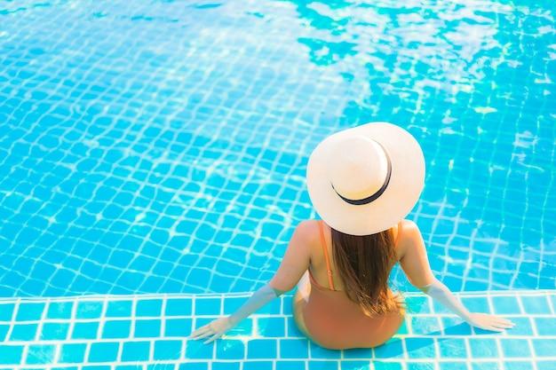 Portret mooie jonge aziatische vrouw ontspannen glimlach vrije tijd rond het buitenzwembad met uitzicht op de zee op de oceaan