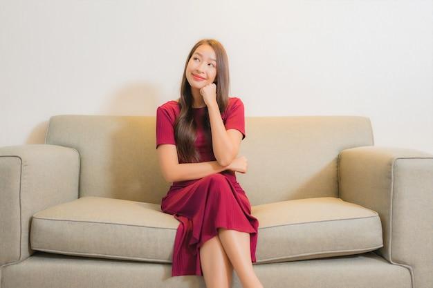 Portret mooie jonge aziatische vrouw ontspannen op de bank in woonkamer interieur