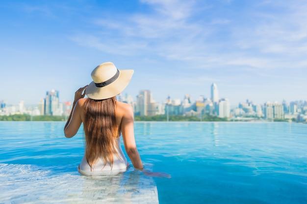 Portret mooie jonge aziatische vrouw ontspannen rond buitenzwembad met uitzicht op de stad