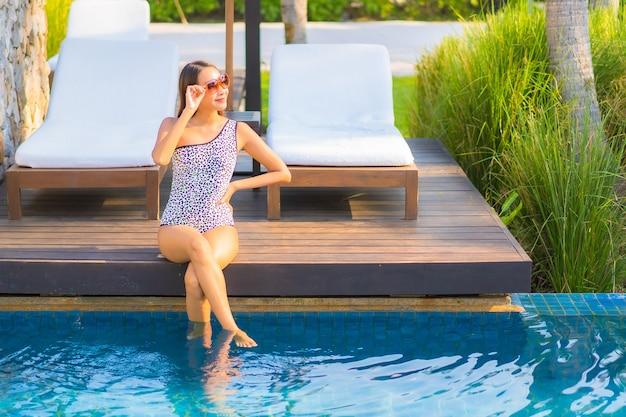 Portret mooie jonge aziatische vrouw ontspannen rond het zwembad in het resorthotel op vakantie