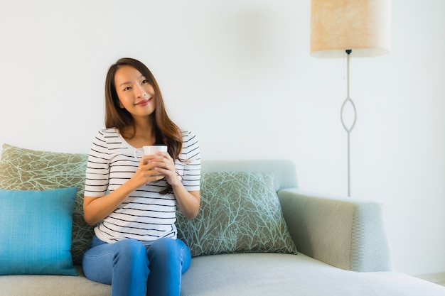 Portret mooie jonge aziatische vrouw op bank met koffiekop