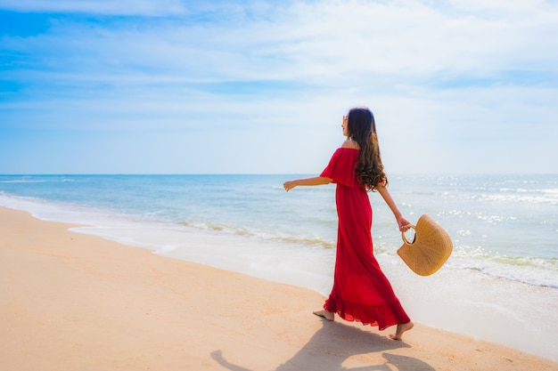 Portret mooie jonge aziatische vrouw op het strand en de zee
