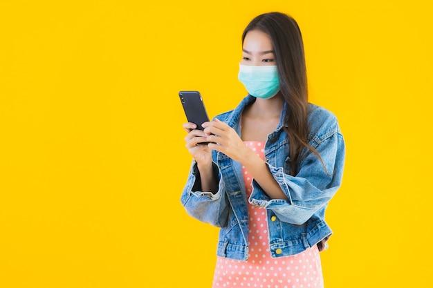 Portret mooie jonge aziatische vrouw slijtage masker gebruik smartphone