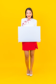 Portret mooie jonge aziatische vrouw toont wit leeg reclamebord op geel geïsoleerd yellow
