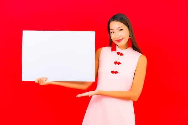 Portret mooie jonge aziatische vrouw toont wit leeg reclamebord op rode muur