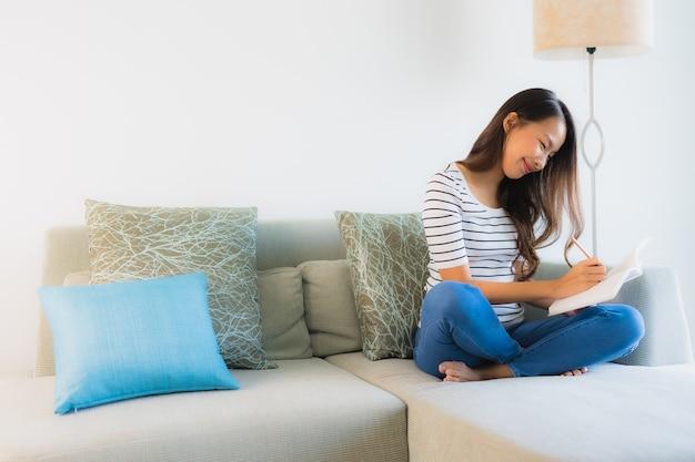 Portret mooie jonge aziatische vrouwen die boek met koffiekop lezen