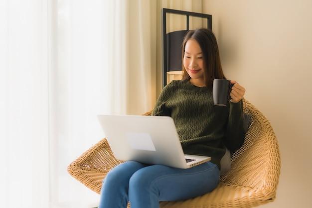 Portret mooie jonge aziatische vrouwen die computer of laptop voor het werken en het zitten op bankstoel met behulp van