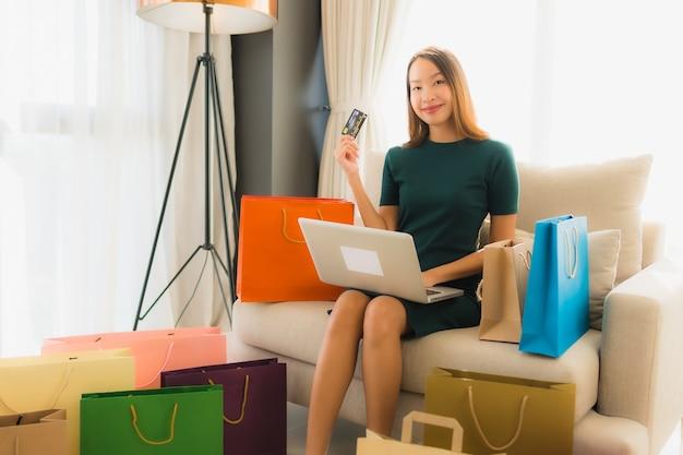 Portret mooie jonge aziatische vrouwen die computerlaptop met creditcard voor online het winkelen met behulp van