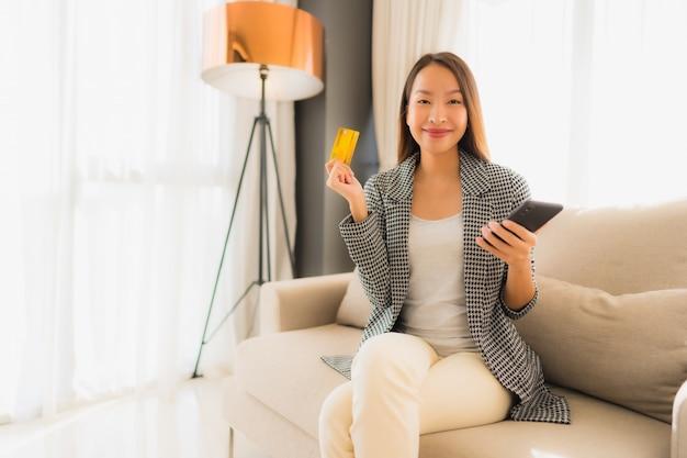 Portret mooie jonge aziatische vrouwen die computerlaptop of slimme en mobiele telefoon met creditcard voor online het winkelen gebruiken