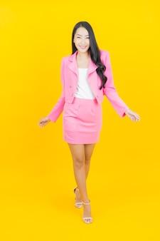 Portret mooie jonge aziatische vrouwenglimlach met actie op gele kleurenmuur