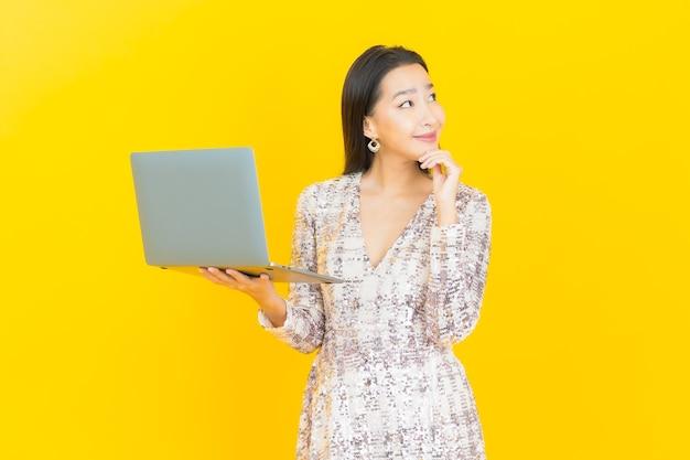 Portret mooie jonge aziatische vrouwenglimlach met computerlaptop op geel
