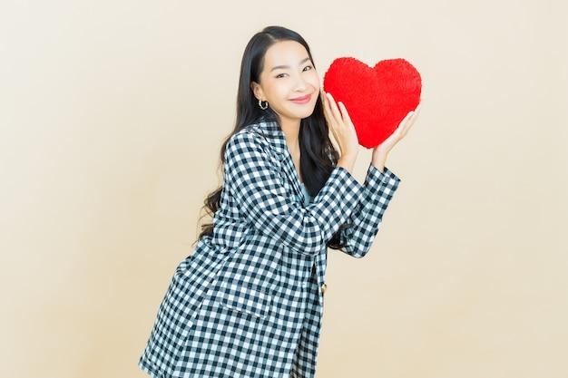 Portret mooie jonge aziatische vrouwenglimlach met de vorm van het hartkussen op beige