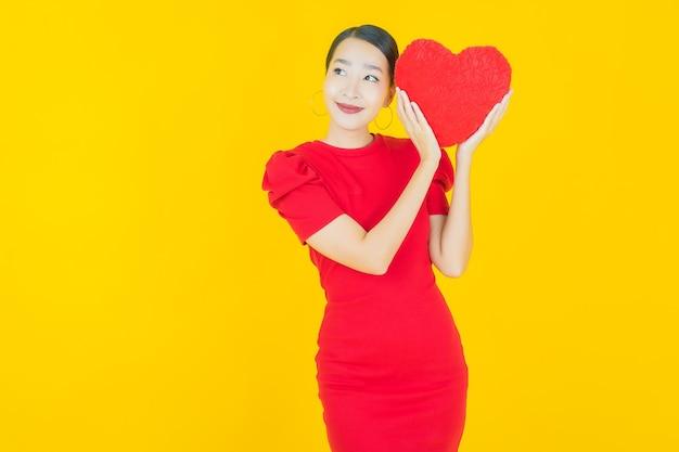 Portret mooie jonge aziatische vrouwenglimlach met de vorm van het hartkussen op geel