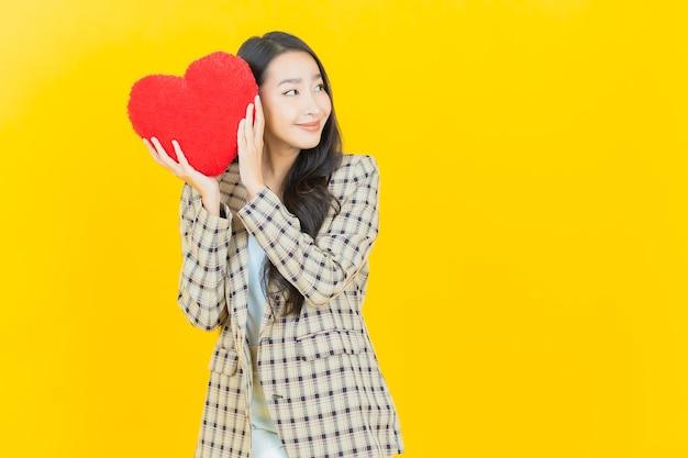 Portret mooie jonge aziatische vrouwenglimlach met de vorm van het hartkussen Gratis Foto