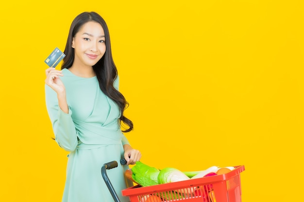 Portret mooie jonge aziatische vrouwenglimlach met kruidenierswinkelmand van supermarkt op geel