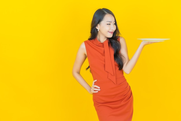 Portret mooie jonge aziatische vrouwenglimlach met lege plaatschotel op geel