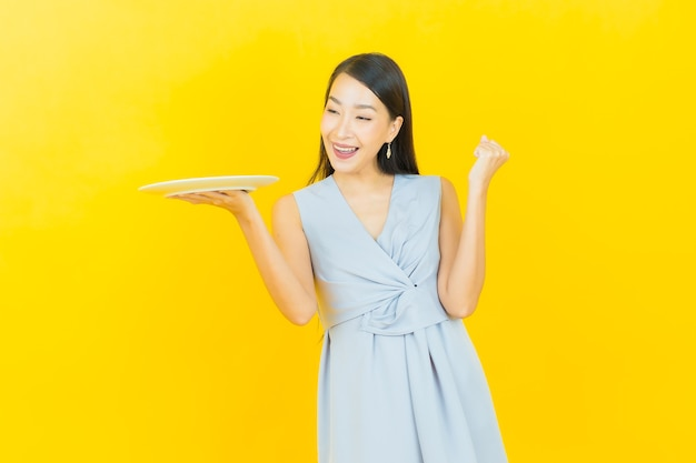 Portret mooie jonge aziatische vrouwenglimlach met lege plaatschotel Gratis Foto