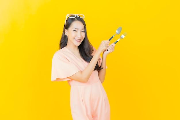 Portret mooie jonge aziatische vrouwenglimlach met lepel en vork op kleurenmuur