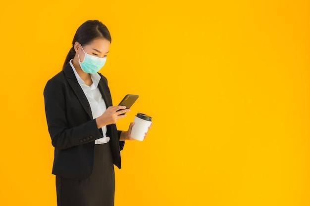 Portret mooie jonge aziatische zaken vrouw slijtage masker gebruik mobiele telefoon met koffie