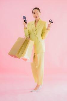 Portret mooie jonge aziatische zakenvrouw met boodschappentas op kleur geïsoleerd