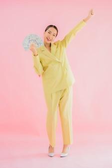 Portret mooie jonge aziatische zakenvrouw met veel contant geld of geld op kleur