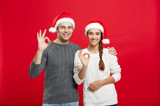 Portret mooie jonge paar weergegeven: ok gebaar met de vinger naar de camera.