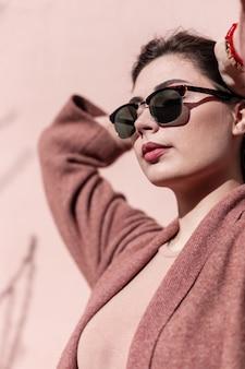 Portret mooie jonge prachtige vrouw in modieuze zonnebril in stijlvolle jas met sexy lippen op straat op zonnige dag. vrij mooi meisje model in stijlvolle kleding poseren in de lentezondag in de stad.