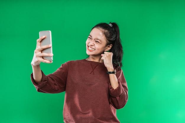 Portret mooie jonge vrouw die iets op de mobiel met een gelukkige uitdrukking op groene achtergrond bekijkt