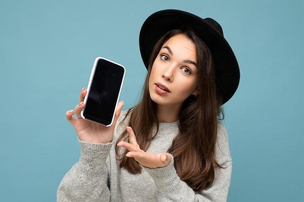 Portret mooie jonge vrouw, gekleed in zwarte hoed en grijze trui met telefoon weergegeven: smartphone