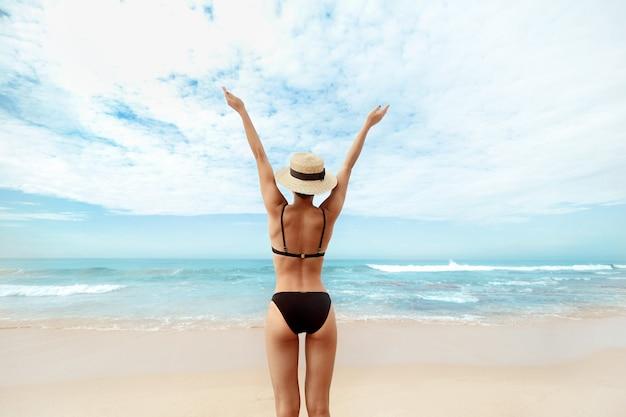 Portret mooie jonge vrouw in bikini met opgeheven handen kijken naar de oceaan achteraanzicht van girl