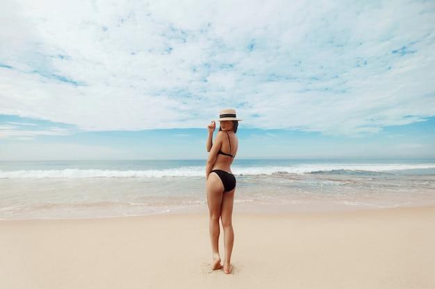 Portret mooie jonge vrouw in bikini op het strand. achteraanzicht van meisje. vrijheidsconcept, vakantie, strand, heldere hemelachtergrond.