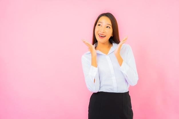 Portret mooie jonge zakelijke aziatische vrouw met actie roze geïsoleerde muur