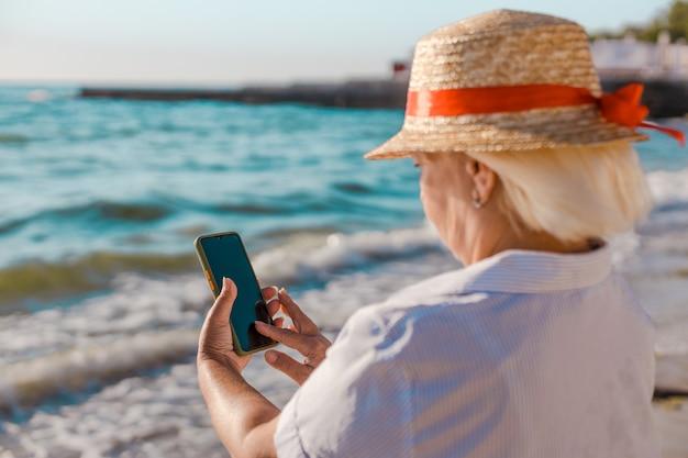 Portret mooie kaukasische blonde vrouw in strooien hoed en gestreept overhemd maakt foto door smartphone van de zee op zonnige dag.