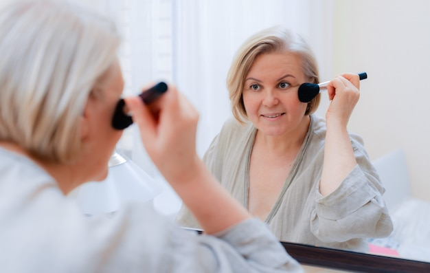 Portret mooie oude vrouw aan te raken haar perfecte huid spiegel kijken. close-up rijpe vrouw gezicht met penseel aanraken van de huid van haar gezicht.